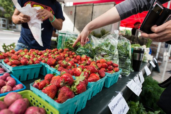 A person selects strawberries from a farmer at a farmer's market.