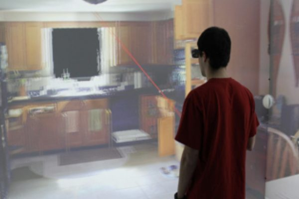 A man uses virtual reality to see a picture of a kitchen.